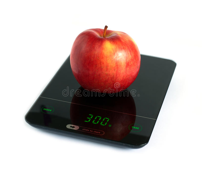 Red apple on kitchen scales isolated on white closeup. Big tasty red apple on kitchen scales isolated on white background. Side view closeup stock images