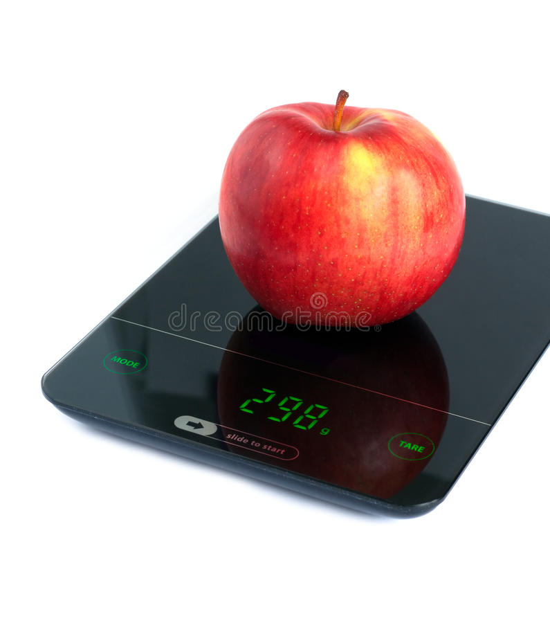 Red apple on kitchen scales isolated on white closeup. Big tasty red apple on kitchen scales isolated on white background. Side view closeup royalty free stock photos