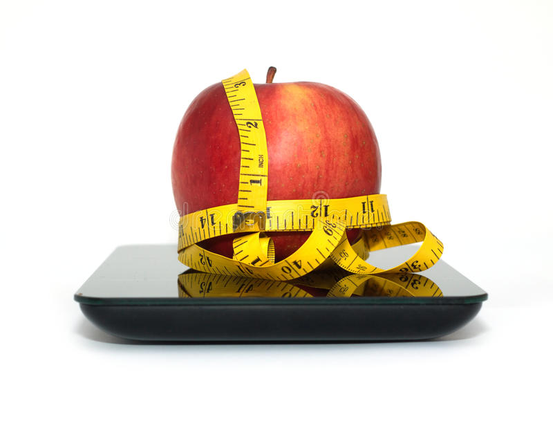 Red apple on kitchen scales with measuring tape isolated closeup. Large tasty red apple on kitchen scales and measuring tape isolated on white background. Front royalty free stock photos