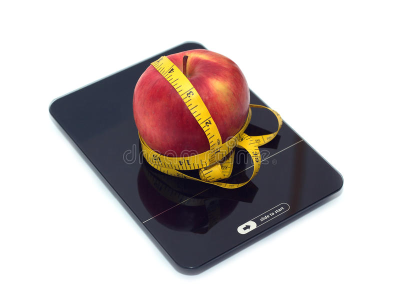 Red apple on kitchen scales with measuring tape isolated closeup. Slide to start new life! Large tasty red apple on kitchen scales and measuring tape isolated on royalty free stock image