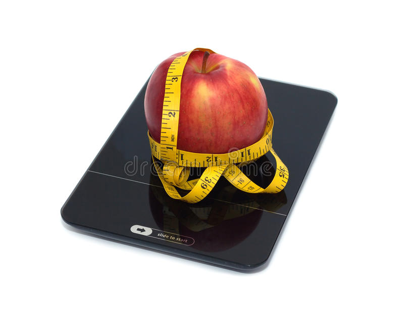 Red apple on kitchen scales with measuring tape isolated closeup. Slide to start new life! Large tasty red apple on kitchen scales and measuring tape isolated on stock photography