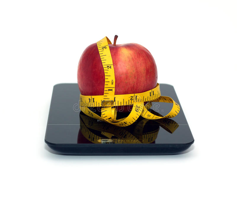 Red apple on kitchen scales with measuring tape isolated closeup. Tasty red apple on kitchen scales and measuring tape isolated on white background. Front view royalty free stock image