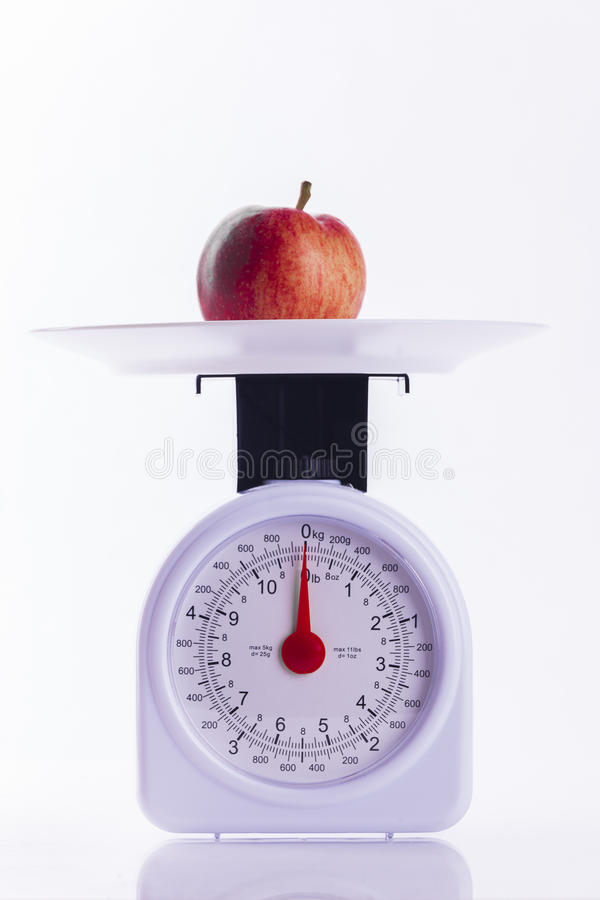 Red apple on kitchen weighing scales on white background. Signifying weight loss and healthy eating stock photos