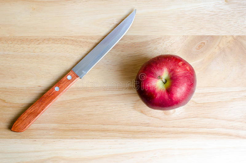 Red apple and knife on wooden table royalty free stock photo