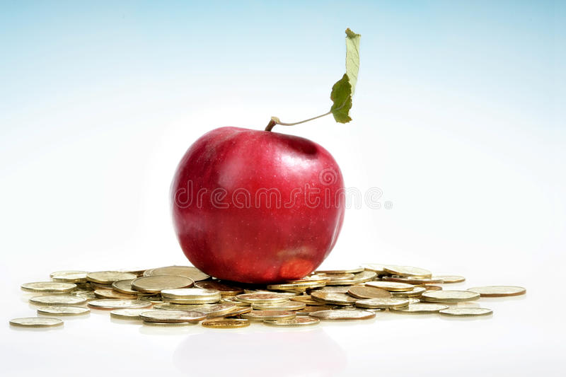 Red apple and a lot of golden coin. Concept of a red apple and a lot of golden coins on white background royalty free stock image