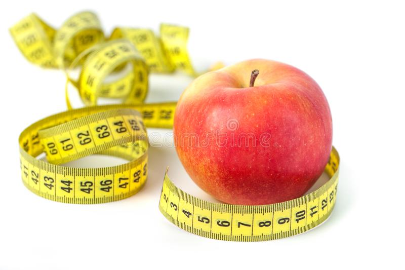 Red apple with measure tape on white background, healthy diet.  royalty free stock photo