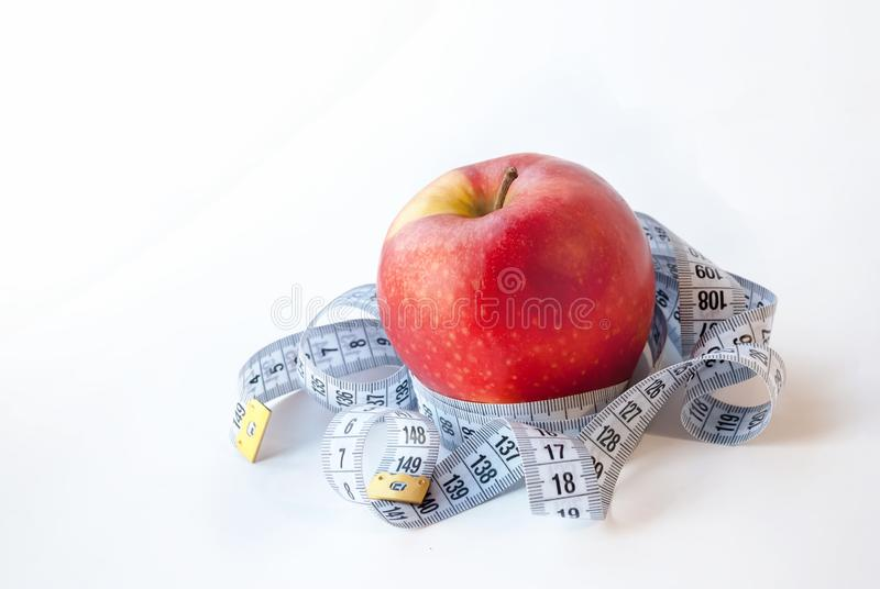 Red Apple and measuring tape on white background. Diet concept royalty free stock photography