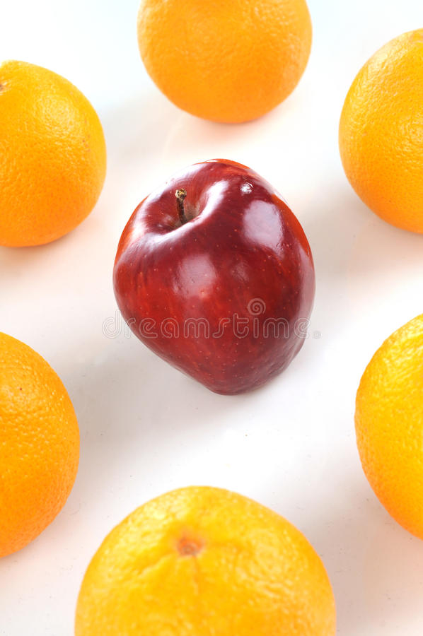 Red apple in the middle of orange. Isolated white background stock image