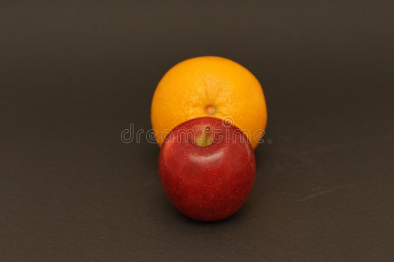 Red apple and orange on black background. Food photography. apple and orange capture in flash light stock photos