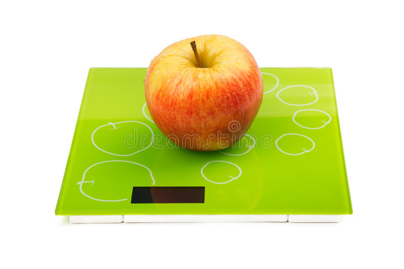 Red apple on scales. Juicy ripe red apple on scales. Isolated royalty free stock images