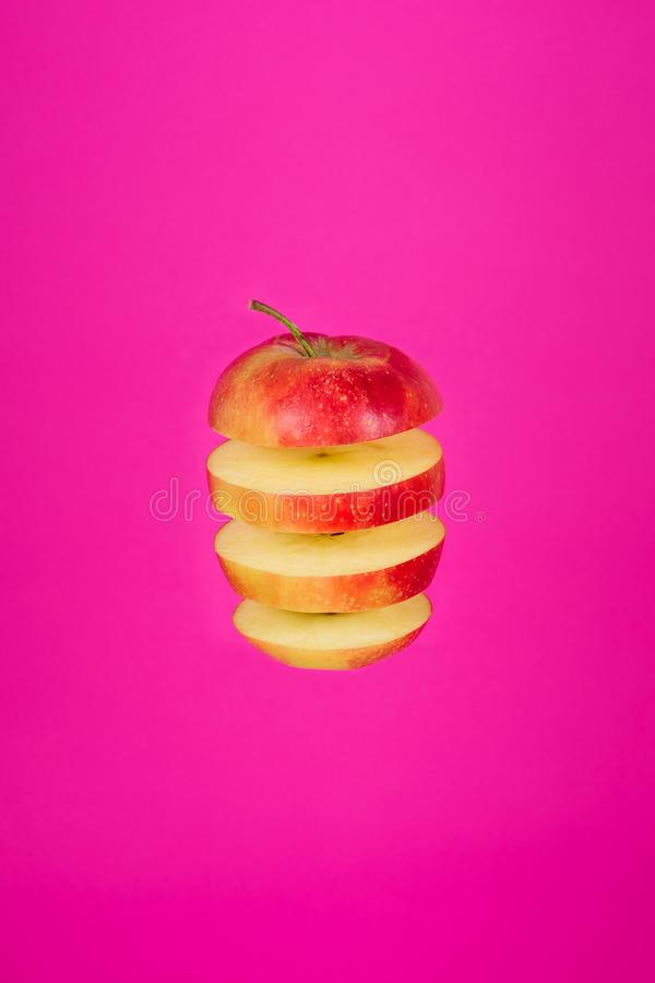 Red Apple Slice Isolated Flying on Pink Background stock photography