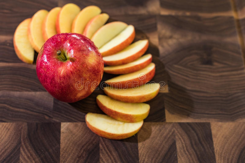 Red Apple with slices. On a cutting board stock image