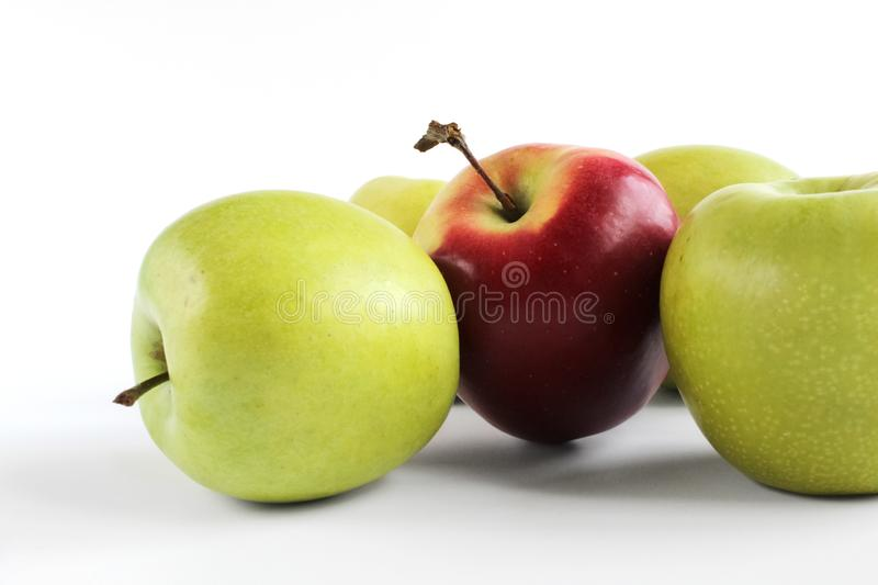 Red apple standing on group of green apples. Green and red apples isolated on white background stock image