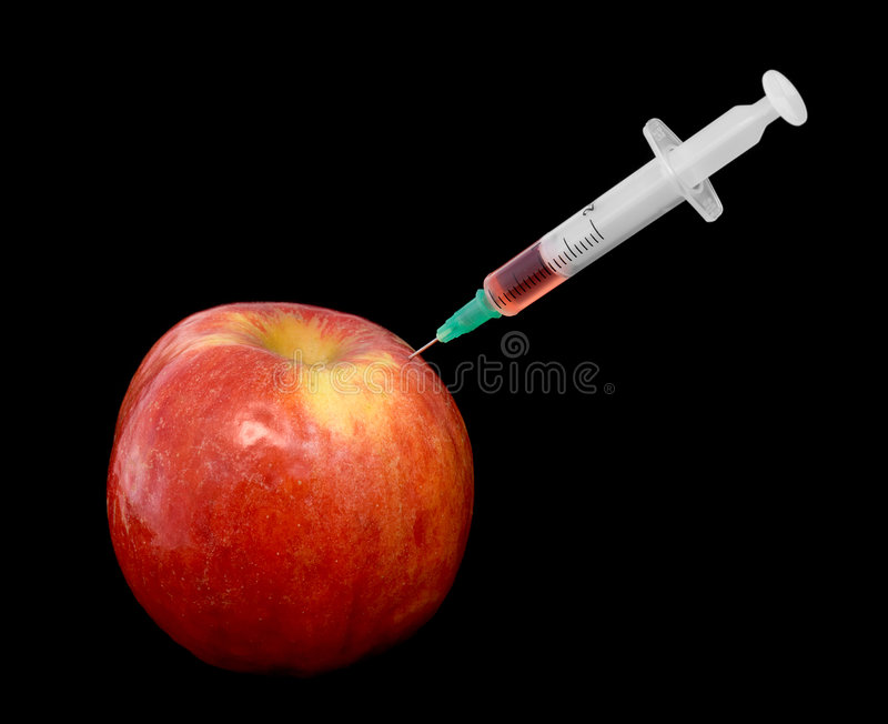 Red apple with a syringe. On a black background stock photography