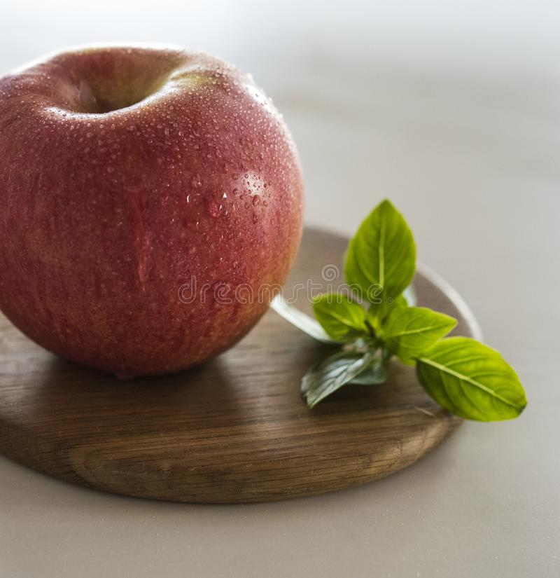 Red apple wet wood board green sheet isolated fruit stock photos