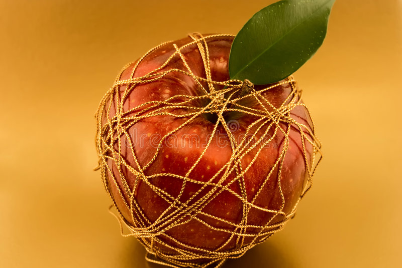 red apple, wrapped gold thread royalty free stock image