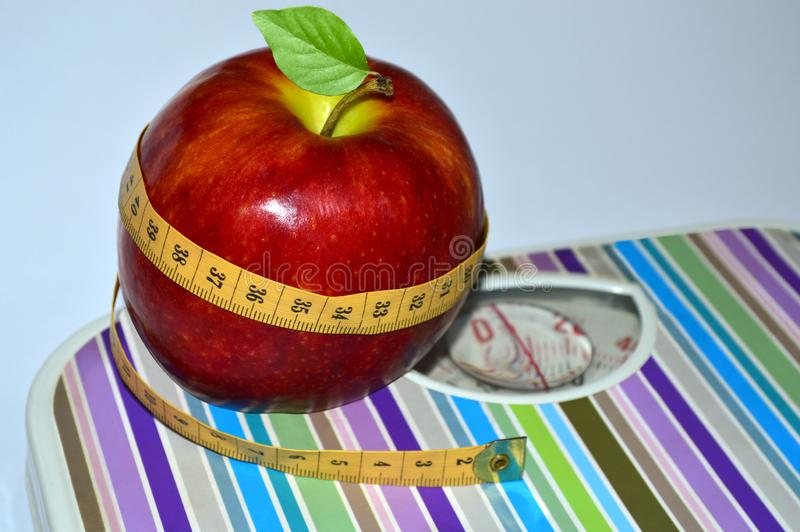 Red apple wrapped with measuring tape on scales. Close up royalty free stock photos