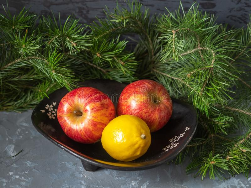 Red apples in a black vase and fir branches on a gray tray. Shot from close range stock image
