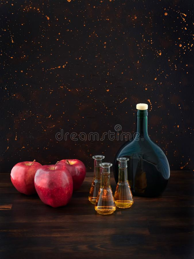 Red apples, glasses of apple brandy or Calvados and a green bottle stock photography