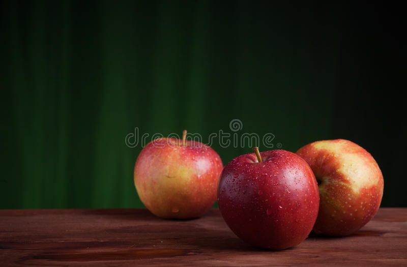 Red apples on a grunge wood and orange background. 3 wet shiny red apples on a grunge wood desk and orange background royalty free stock photography