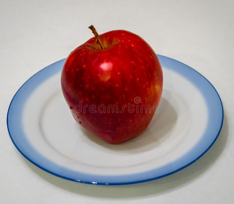 Red apples lie on a plate royalty free stock image