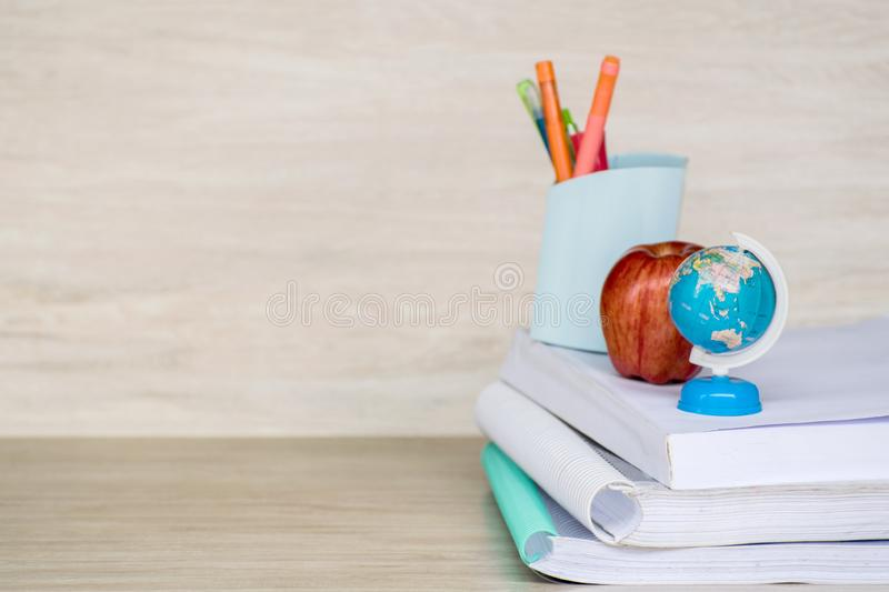 Abstract education, red apples, multicolored pens and white books with wooden backgrounds. Red apples, multicolored pens and white books with wooden backgrounds stock image