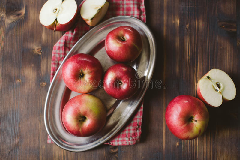 Red apples on plank wooden table. Metal plate stock photos