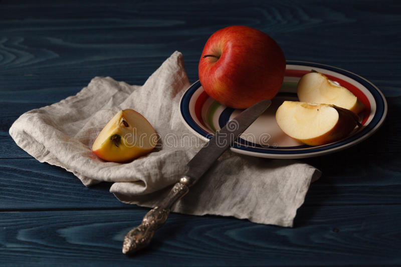 Red apples with slices over blue wooden background stock photos