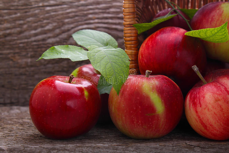 Red apples spill out of the basket. On a dark wooden background royalty free stock images