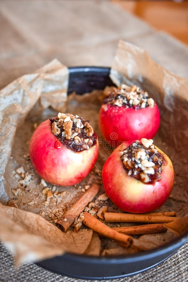 Red apples stuffed with jam and nuts ready for baking with cinnamon flavor stock image