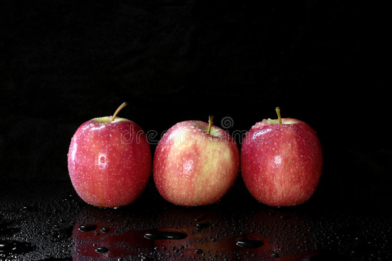 Red apples. Three red apples in a row on dark background and copy space stock photo