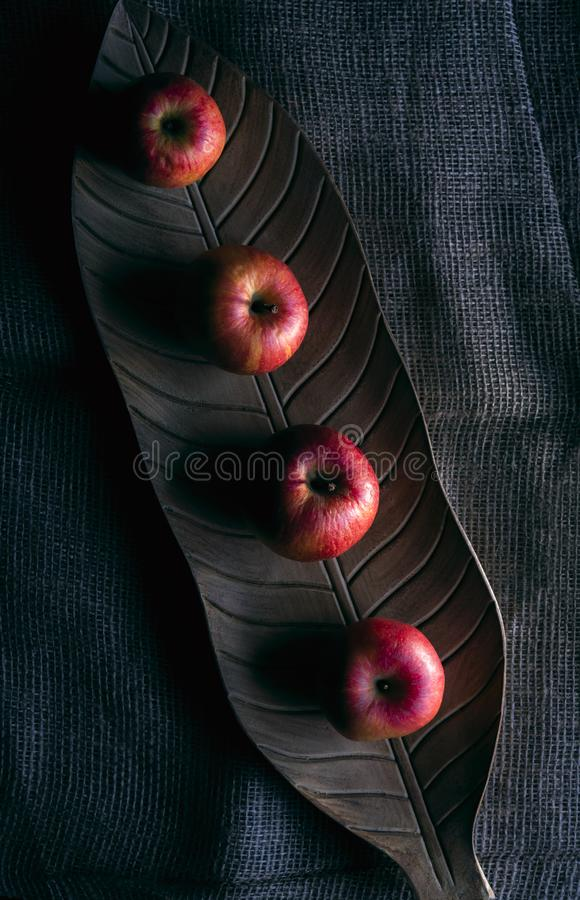 Red apples on a wooden tray in low light stock photo