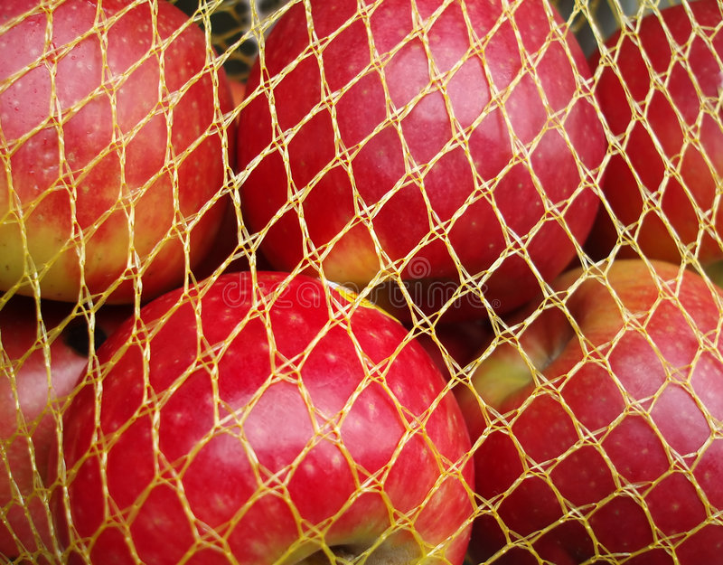 Red apples in yellow net royalty free stock image