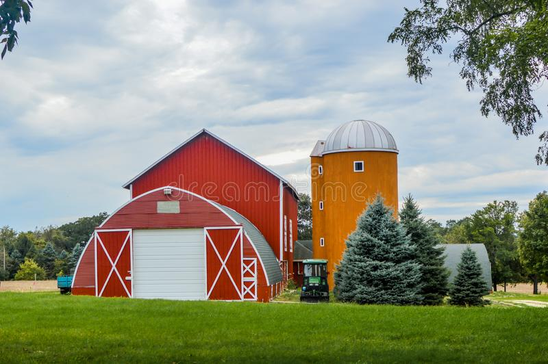 Red Arched Barn with Orange Twin Silos royalty free stock images