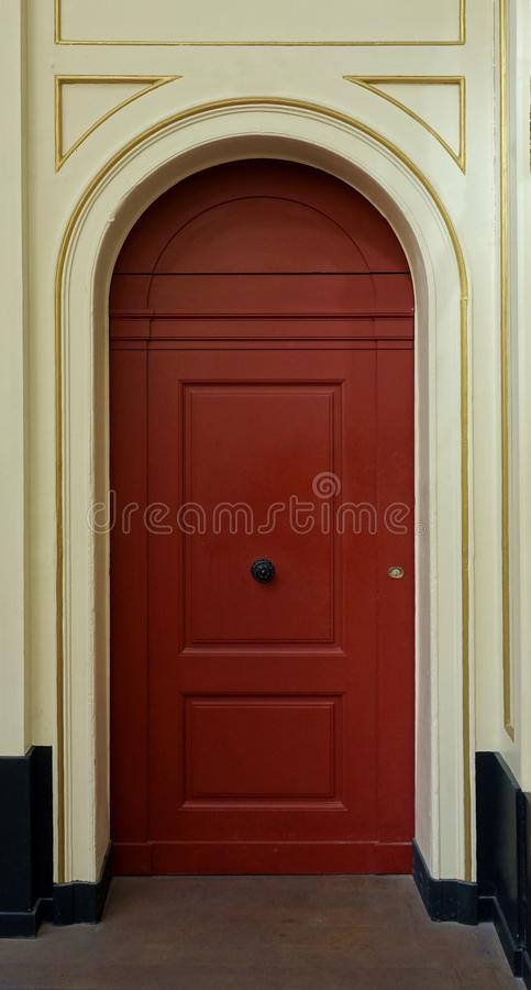 Red Arched Door with Golden Trim Details royalty free stock photo