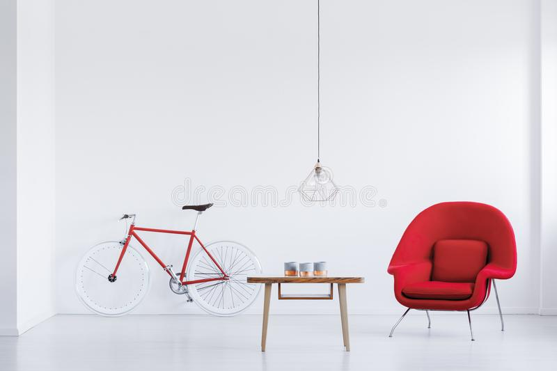 Red armchair in bright apartment royalty free stock image