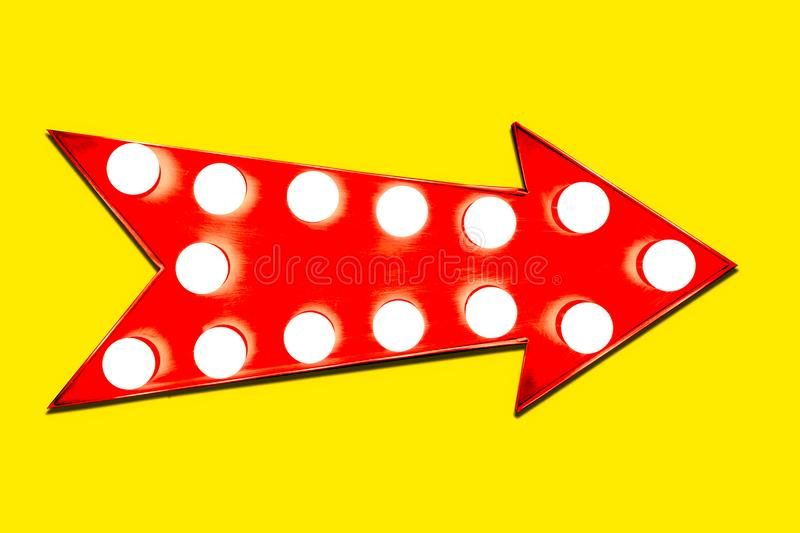 Red arrow shaped vintage colorful illuminated metallic display direction sign with glowing light bulbs on an intense vivid yellow. Background royalty free stock photos