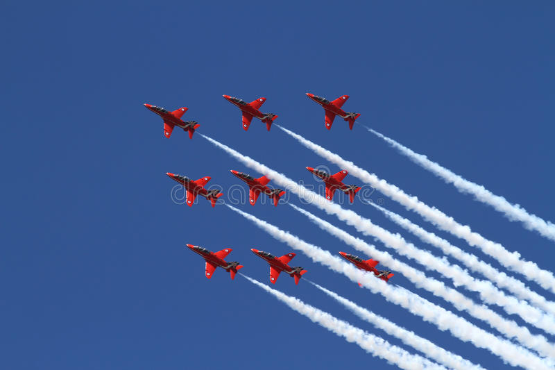 Red Arrows Display Team. British Royal Air Force Red Arrows Display Team flying in formation, with White smoke royalty free stock image