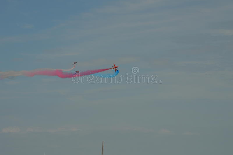 Red arrows. Orbiting each other with flag colour smoke spiral stock photography