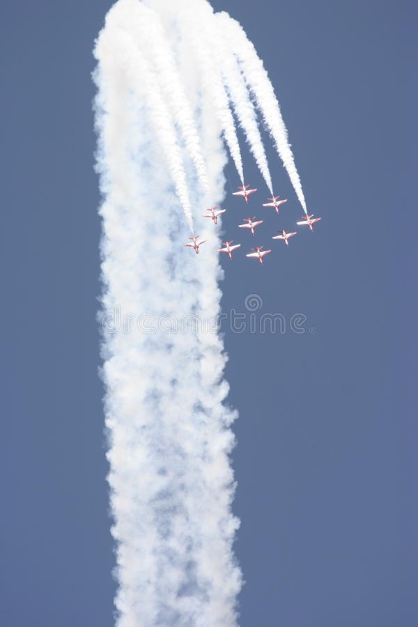 The Red Arrows RAF aerobatic team in smoked arch. The Red Arrows in smoked arch against a clear blue sky. The Royal Air Force Aerobatic Team, the Red Arrows, is stock images
