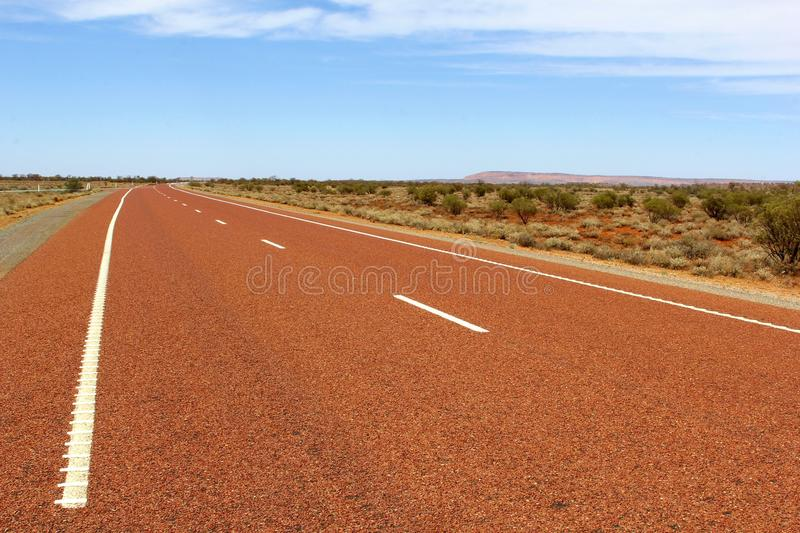 Red abandoned highway in the countryside, Australia. A divided red asphalt highway and verges of a road goes through a natural landscape in the plain. Stuart stock photo