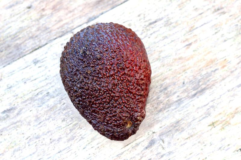 Red avocado on a background of pure ancient wood royalty free stock image