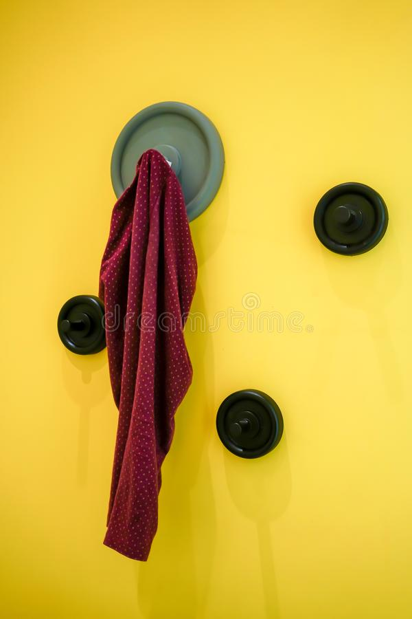 Red baby pants hanging on modern grey wall hook mounted. On bright yellow wall stock image