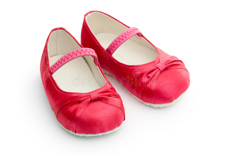 Red baby shoes. Red satin baby shoes against a white background royalty free stock photo