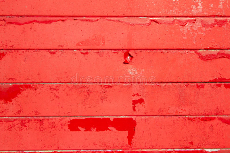Red background. A background made of horizontal wooden slats painted in red flaking paint royalty free stock images