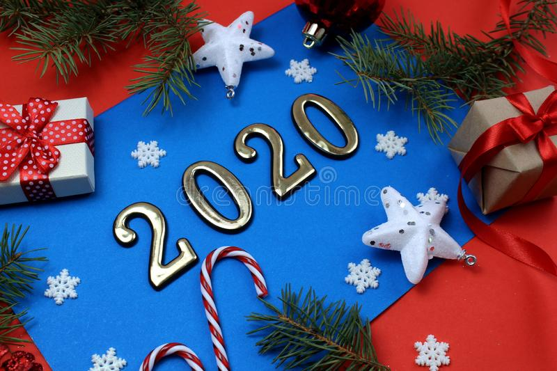 On a red background a blue sheet with Christmas decorations and a box with the inscription 2020 stock image