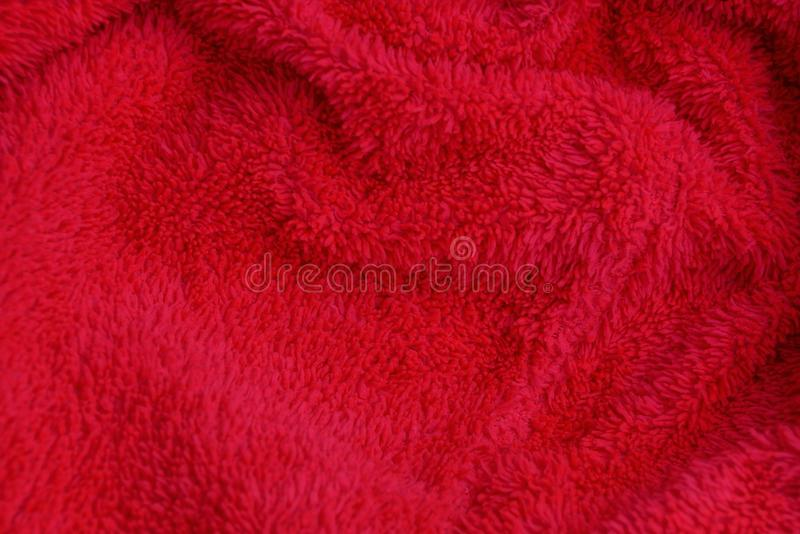 Red fabric texture from crumpled fur on clothes. Red background of crumpled fur on clothes royalty free stock photography