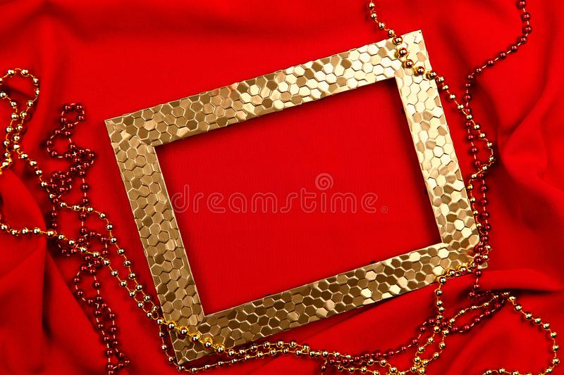 Red background. Golden and red beads, photo frame. royalty free stock photos