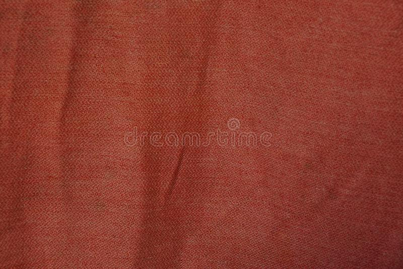 Red fabric texture from a piece of crumpled matter on clothes. Red background of a piece of crumpled matter on clothes royalty free stock photos