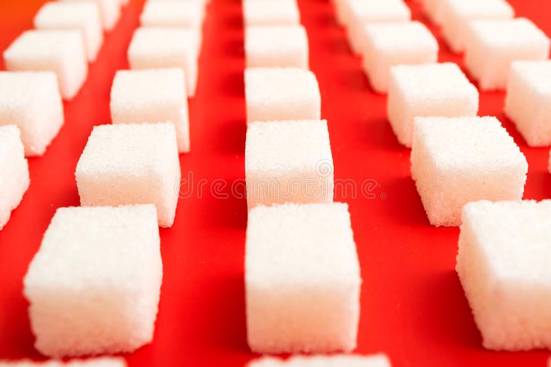 On a red background white slices of sugar. Rows of sugar royalty free stock images